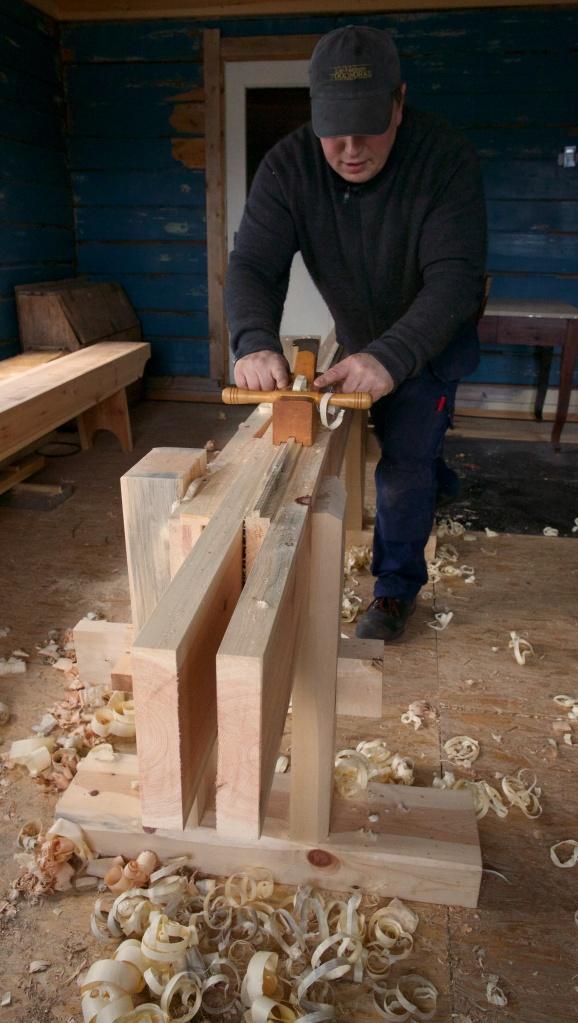 Pløying av golvbord på skottbenk. Meiane på høvelen botnar på langborda på skottbenken og sikrar at kanten av golvbordet vert bein. Foto: Roald Renmælmo